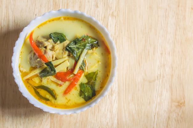 Kip curry met bamboo shoots in witte kom op de houten tafel.