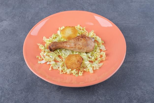 Kip drumstick en gebakken aardappelen op oranje plaat.