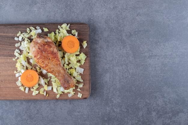 Kip drumstick en gesneden groenten op een houten bord.