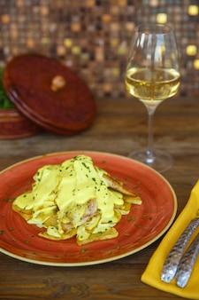 Kip en aardappel met bechamelsaus geserveerd met witte wijn