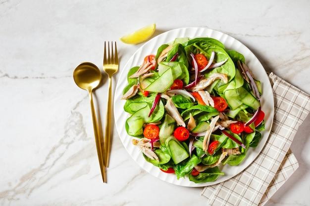Kip- en groentesalade met verse babyspinazieblaadjes, cherrytomaatjes, komkommerlinten, ui met olijfolie en citroendressing, geserveerd op een bord op een witmarmeren stenen tafel, vrije ruimte