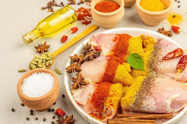 Kip en kerrie kruiden. set van grondstoffen voor het koken van traditionele gerechten. lichte stenen betonnen achtergrond, close-up