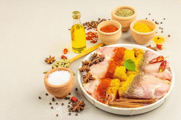 Kip en kerrie kruiden. set van grondstoffen voor het koken van traditionele gerechten. lichte stenen betonnen achtergrond, kopieer ruimte