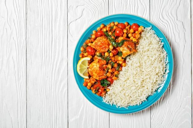 Kip- en kikkererwtencurry en jasmijnrijst met cherrytomaatjes, spinazie, gele currypasta geserveerd op een blauw bord met een schijfje citroen op een witte houten tafel, bovenaanzicht, close-up, kopieerruimte