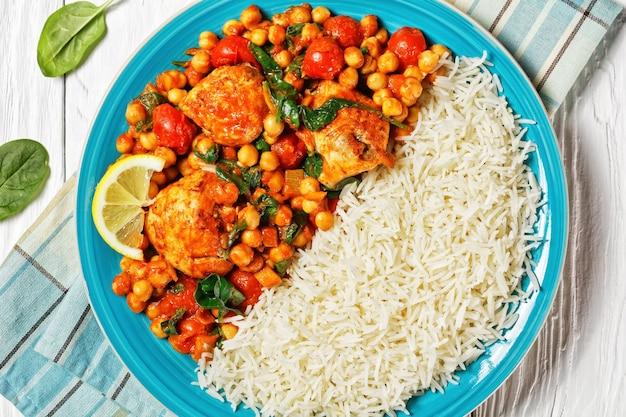 Kip en kikkererwtencurry geserveerd met jasmijnrijst met kerstomaatjes, babyspinazie, gele currypasta geserveerd op een blauw bord met een schijfje citroen op een witte houten ondergrond, bovenaanzicht, close-up