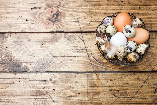 Kip en kwartelseieren in een plaat op een houten achtergrond. ruimte kopiëren