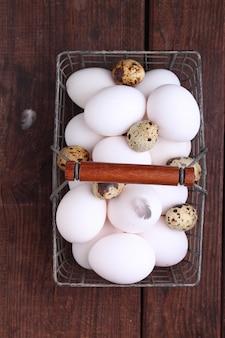 Kip en kwartelseieren met veren in een metaalmand