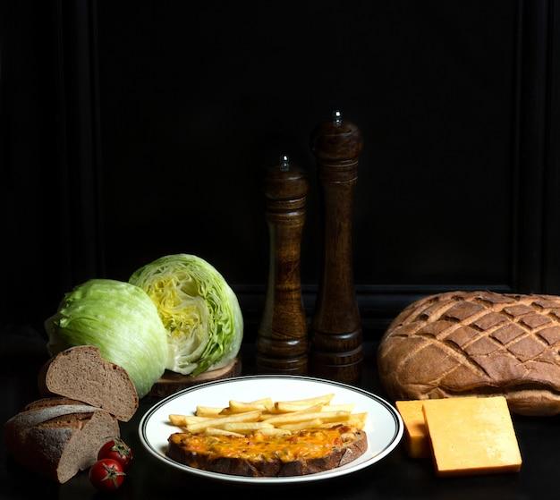 Kip en tomaten gegarneerd met geraspte kaas op brood en frietjes