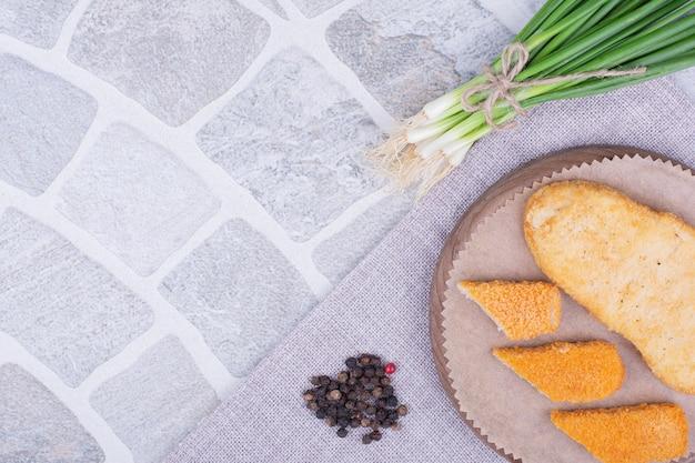 Kip en vis nuggets op een houten bord met groene uien