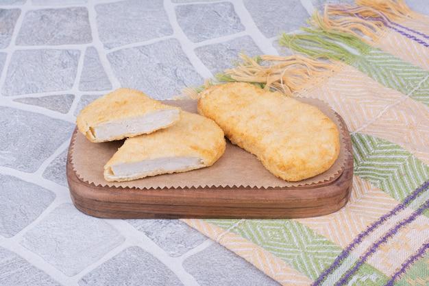 Kip en visnuggets op een houten bord.