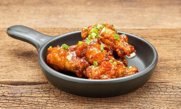 Kip geroerbakt met pikante saus bestrooid met witte sesam en gehakte lente-uitjes wordt in een zwarte keramische pan op een houten tafel geplaatst.