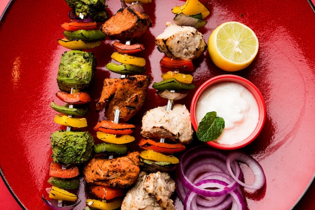 Kip hariyali kakab of malai malai kebab in driekleur geserveerd met spiesjes en yoghurtdip in een bord