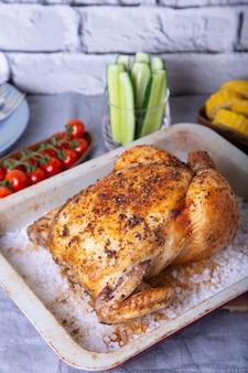 Kip heel gebakken op zout. met maïskolven, kerstomaatjes, komkommers en jalapenopepers. selectieve focus, close-up.