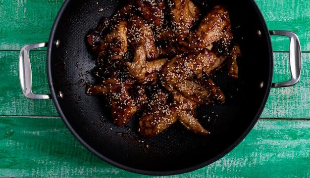 Kip in teriyakisaus in een wok pan close-up, bovenaanzicht