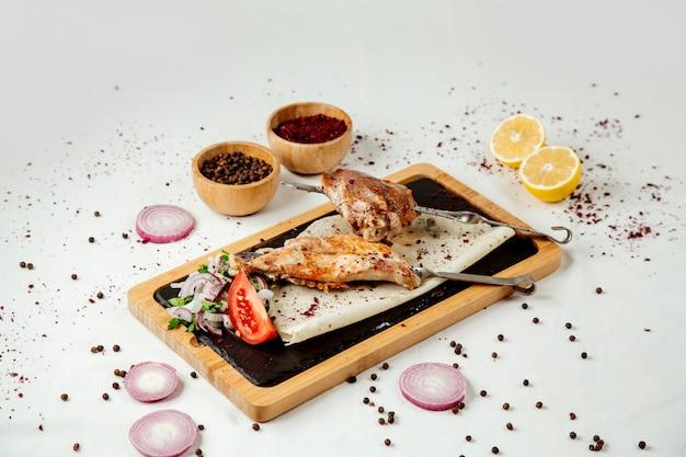 Kip kebab op chompur met uien op een houten bord