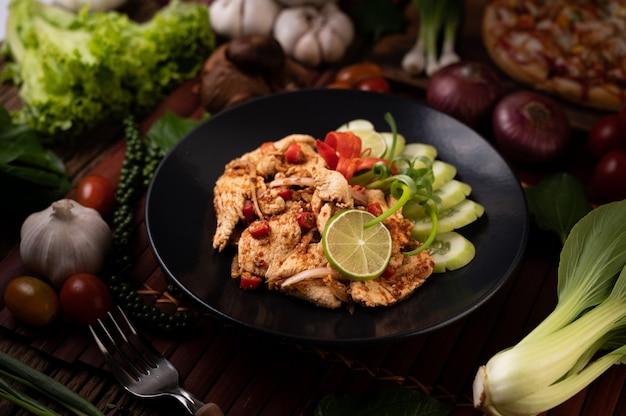 Kip larb op het bord met gedroogde pepers, tomaten, lente-uitjes en sla
