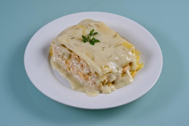 Kip lasagne in witte schotel geïsoleerd op neutrale achtergrond.