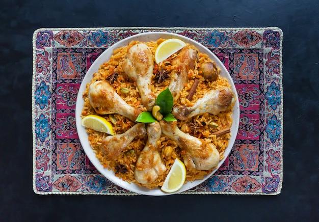 Kip mandi met dadels op een zwarte tafel. arabische keuken. bovenaanzicht