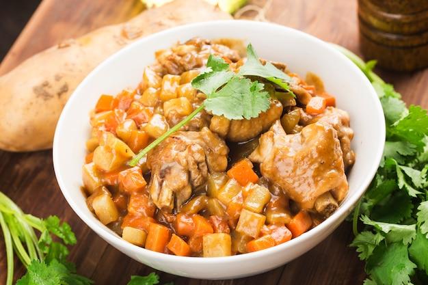 Kip met aardappel en wortel in kerrie,