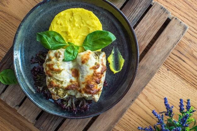 Kip met aardappelpuree en jus op houten