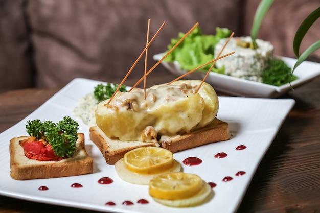 Kip met champignons in aardappel op toast brood tomaten citroensaus zijaanzicht