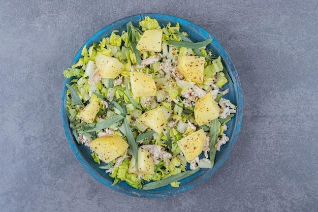 Kip met gekookte aardappelen op blauw bord.