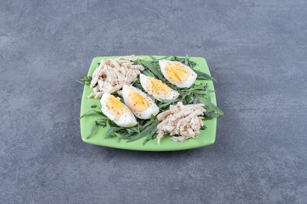 Kip met gekookte eieren op groene plaat.