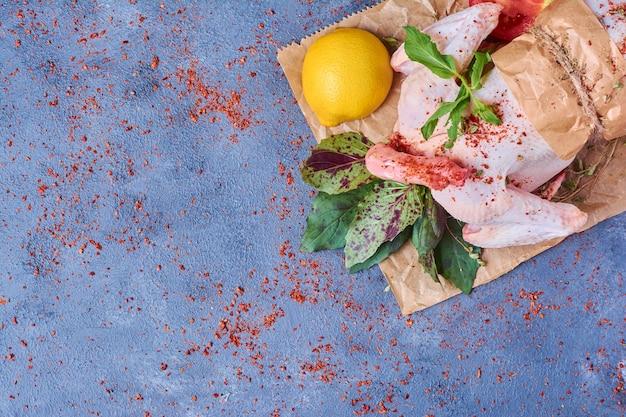 Kip met kruiden op een houten bord op blauw