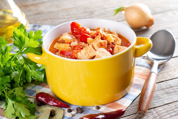 Kip paprikash - traditionele hongaarse kip gekookt in paprika en roomsaus, met ingrediënten op houten achtergrond