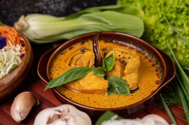 Kip rode curry in een kom met gedroogde pepers, basilicum, komkommer en kousenband
