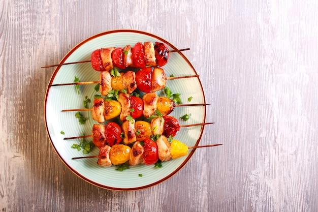 Kip, rode en gele tomatenbrochettes op plaat