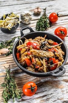 Kip roerbak in een pan. wok udon-noedels. traditioneel aziatisch eten. witte achtergrond. bovenaanzicht.