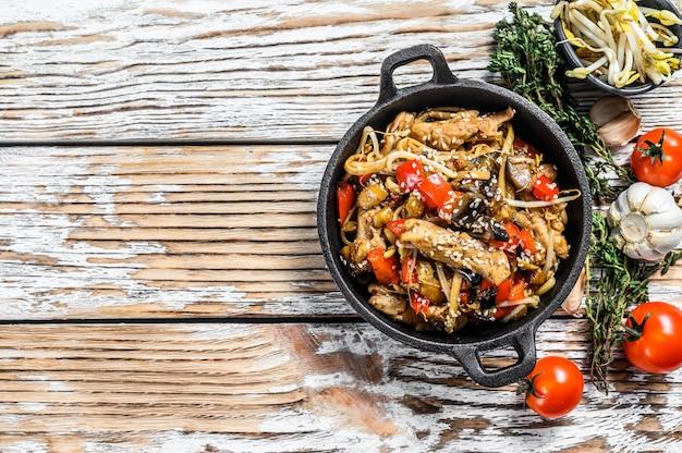 Kip roerbak in een pan. wok udon noedels. traditionele aziatische gerechten op wit. bovenaanzicht. kopieer ruimte