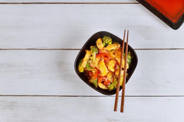 Kip roerbak met groente in zwarte kom met eetstokje