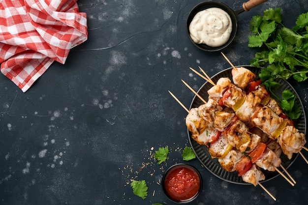 Kip shish kebab of spiesjes kebab op een houten bord, specerijen, kruiden en groenten