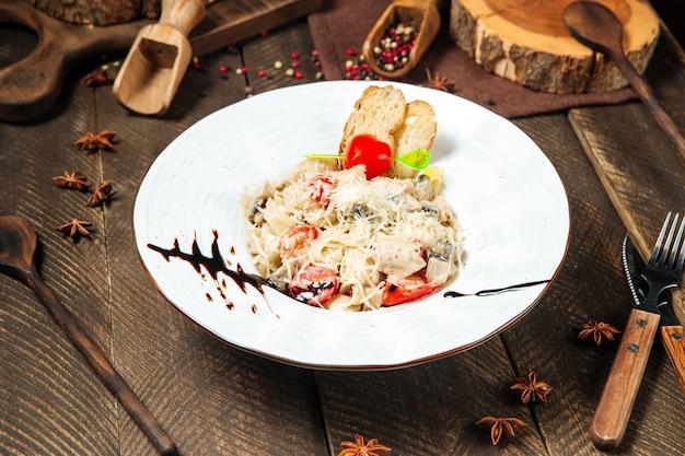 Kip tagliatelle met champignons op de houten tafel