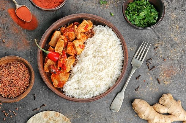 Kip tikka masala met rijst in houten kom en ingrediënten op tafel