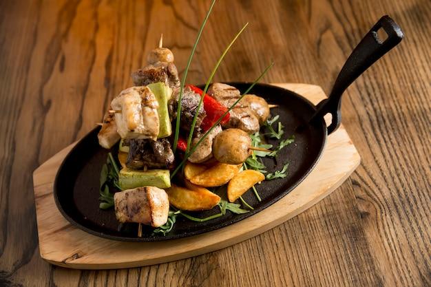 Kip-, varkens- en rundvleesspiesjes met groenten en pikante aardappelen