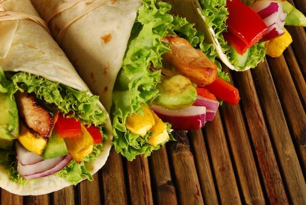 Kip wrap sandwiches op een houten mat