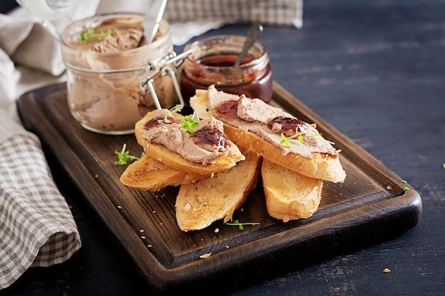 Kip zelfgemaakte leverpasta in glazen pot met toast en bosbessensap jam met chili