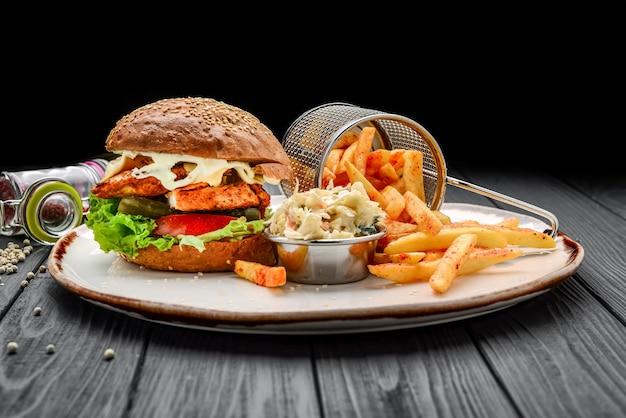Kipburger met aardappelen en koolsalade. op een zwarte houten ondergrond