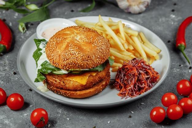 Kipburger met frietjes en salade op een oud beton.