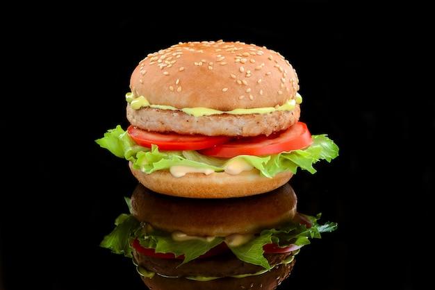 Kipburger met kaassaus en tomaat op een zwarte ondergrond