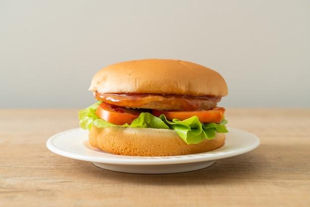 Kipburger met saus op wit bord