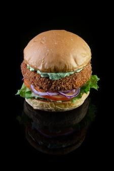 Kipburger met sla, tomaat, paarse ui en handgemaakte mayo op zwarte backgorund. heerlijk.