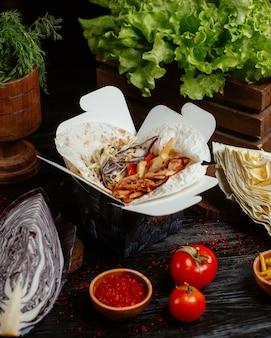 Kipfajitas met salade in lavash, afhaalmaaltijden geserveerd met groenten.