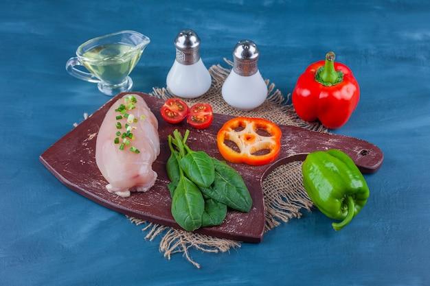 Kipfilet en groenten op een snijplank, geen jute servet, op de blauwe tafel.