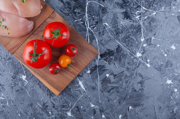 Kipfilet en tomaten op een bord, op de blauwe achtergrond.