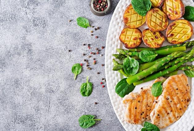 Kipfilet gekookt op een grill met een garnituur van asperges en gebakken aardappelen. dieet menu. gezond eten. plat leggen. bovenaanzicht