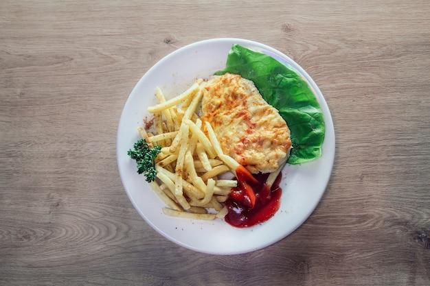 Kipfilet in kaas en frietjes op wit bord